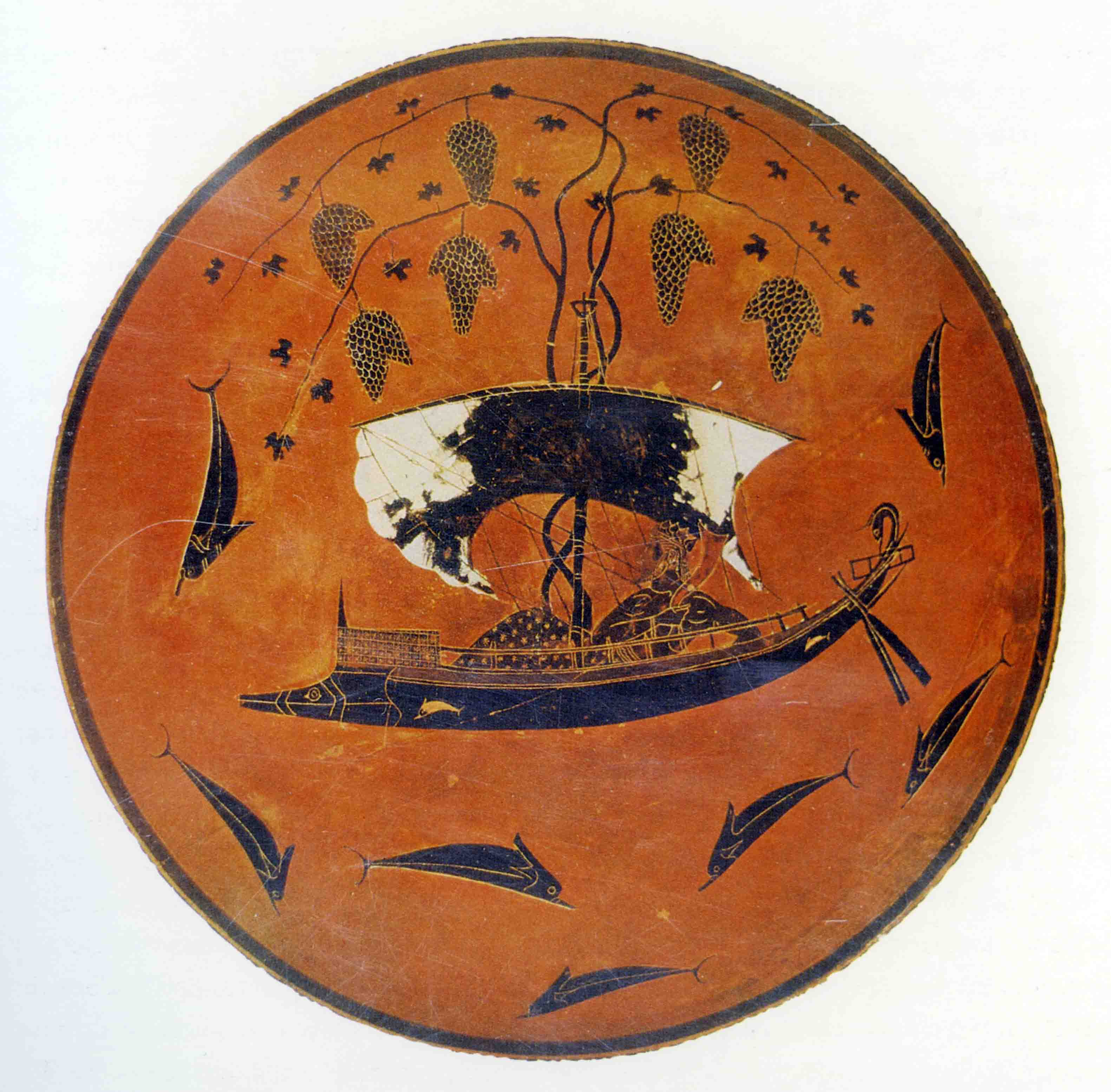 02. Dioniso attraversa il mare. Dipinto a figure nere su kylix da Vulci, 540 a.C. circa. La leggenda vuole che il dio, rapito dai pirati, avrebbe fermato la nave con i tralci della vite e trasformato i remi in serpenti. I marinai terrorizzati si sarebbero lanciati in mare, mutandosi in delfini. (Monaco, Staatliche Antikensammlungen).